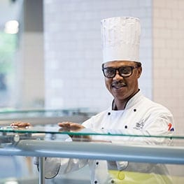 Male chef smiling in dining hall