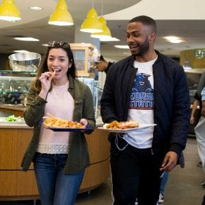 Male and female walking with food in dining hall